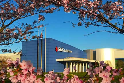 Photo of the R&K Building surrounded by flowers