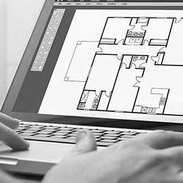 Photo of hands touching a laptop with a CAD drawing of a floor plan